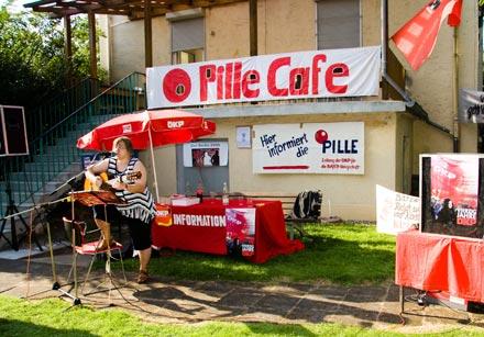 Viel Rot: Großes Transparent am Haus der Kulturvereinigung Leverkusen: Pille Café, ein verwaister Diskussionstisch davor die Künstlerin mit Gitarre.