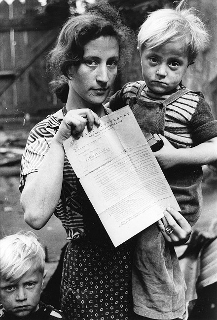 Mutter mit zwei traurig blickenden Kindern hält amtliches Schreiben in der Hand.