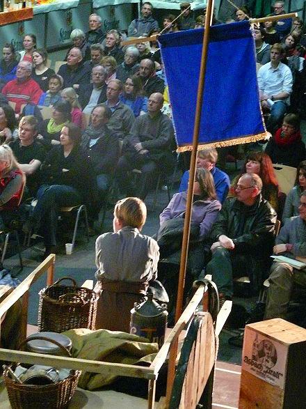 Mutter courage auf dem wagen sitzend vor dem publikum in der